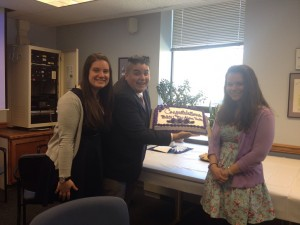 President Joe Faykosh presents the Phi Alpha Theta cake with new member Ally Schmidt and Lanna Demers