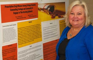 Terry Rentner's stands next to the poster that was presented at the Society for Public Health Education conference in Baltimore.