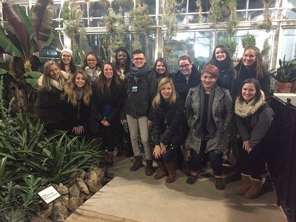 A group of BGSU PRSSA members pose for a photo with former BGSU PRSSA President Lucas Stall (center) at his job at the Toledo Zoo. Stall, who runs all social media for the Zoo,  gave the group a behind the scenes tour of the Lights Before Christmas.