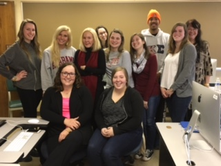 Group photo of Katherine Boo with  the Public Affairs Reporting class, spring 2016. Sitting in front: Lily Bartell and Hannah Benson. Back row: Sami Fisher, Megan Kraft, Katherine Boo, Audrey Quinn, Jessica Speweike, Annie Furia, Aaron Parker, Marissa Barenbrugge and Nancy Brendlinger. Photo by Catherine Cassara
